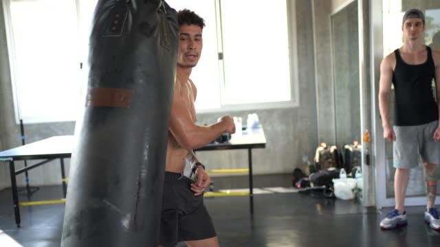man boxer punching combat bag - kickboxing stock videos & royalty-free footage