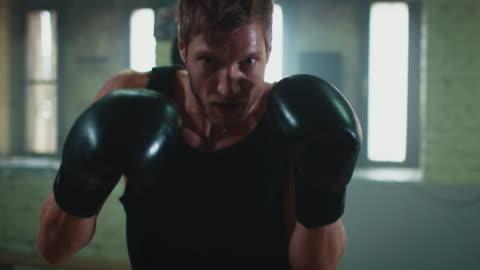 mann punshing boxsack - haut stock-videos und b-roll-filmmaterial