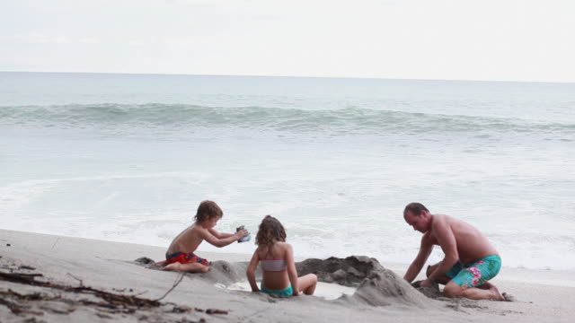 vídeos de stock, filmes e b-roll de ms man, boy and girl build sandcastle on beach with wave break and rocks  / montezuma, puntarenas, costa rica - kelly mason videos