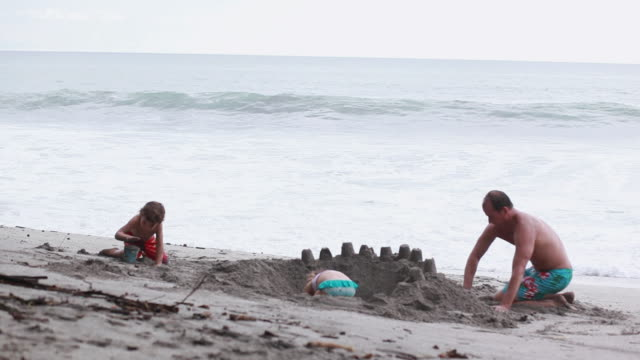 ms man, boy and girl build sandcastle on beach with wave break / montezuma, puntarenas, costa rica - digging stock-videos und b-roll-filmmaterial