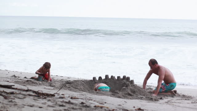vídeos de stock, filmes e b-roll de ms man, boy and girl build sandcastle on beach with wave break / montezuma, puntarenas, costa rica - kelly mason videos