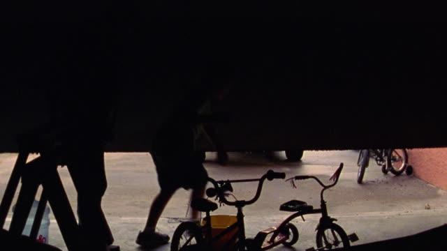 vídeos y material grabado en eventos de stock de rear view man + boy exiting garage with hose + bucket walking towards suv - garaje