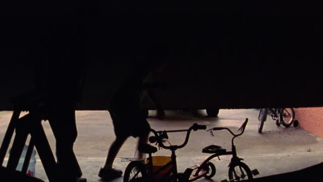REAR VIEW man + boy exiting garage with hose + bucket walking towards SUV