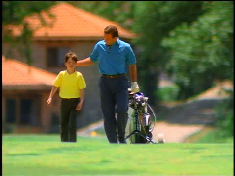 Man + boy pulling golf bag walk toward camera on golf course / man rubs boy's head