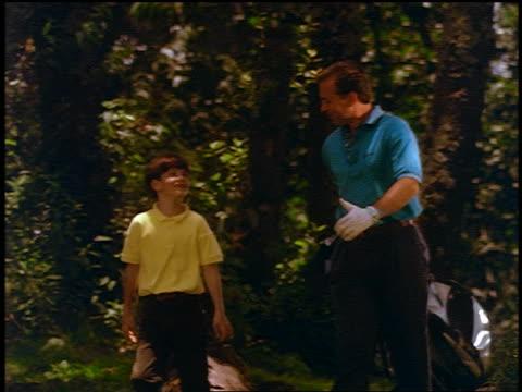 Man + boy pulling golf bag walking down hill on golf course