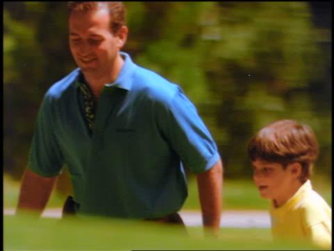 PAN man + boy pulling golf bag walking up hill on golf course