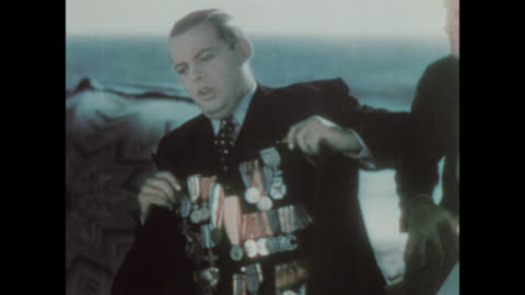 1930 man bragging to his friend's on the beach, showing off his many medals - medal stock videos & royalty-free footage