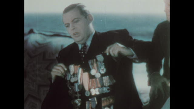 vidéos et rushes de 1930 man bragging to his friend's on the beach, showing off his many medals - médaille récompense