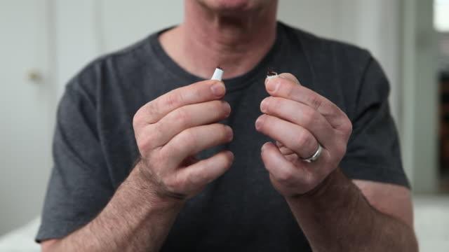 vídeos de stock e filmes b-roll de man breaking cigarette - cigarro
