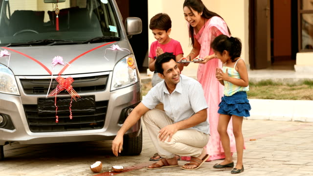 MS Man breaking coconut on ground with his family for a new car / Sonipat, Haryana, India