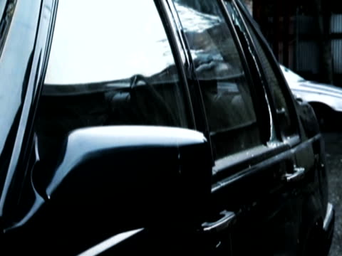 man breaking into a car with a crowbar, opening the door, stealing a jacket and escaping - londonalight点の映像素材/bロール