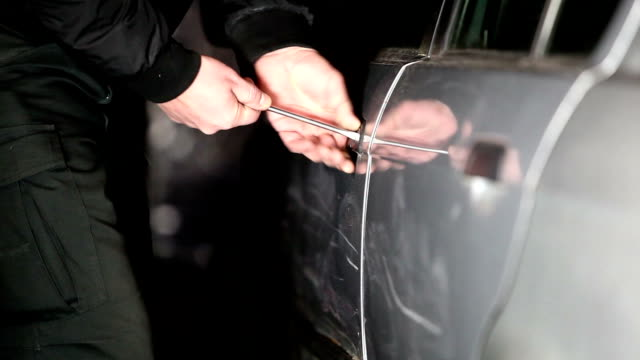 man breaking into car using screwdriver - thief stock videos & royalty-free footage