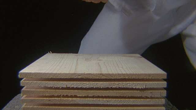 SLO MO, CU, Man breaking stack of wood with karate chop, close-up of hand