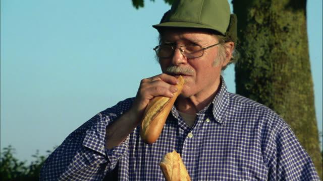 A man breaks a baguette.
