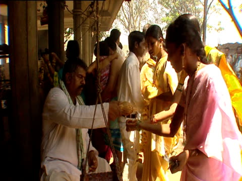 stockvideo's en b-roll-footage met a man breaks a coconut and gives the juice to women to drink during rituals in temple - gelovige