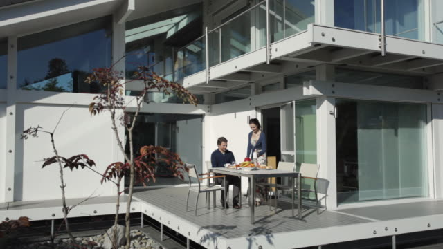 ws pan man bringing breakfast bread rolls to table on porch, woman serving coffee / kleinmachnow, brandenburg, germany - front stoop stock videos and b-roll footage