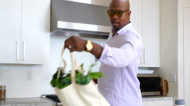 ws man bringing canvas bags with groceries into kitchen after shopping - modern manhood stock videos & royalty-free footage