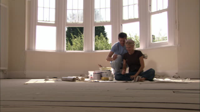 vídeos de stock e filmes b-roll de man bringing drink to woman seated on floor / they discuss diy project as woman draws plan of room - sentar se