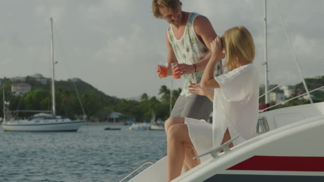 vídeos de stock, filmes e b-roll de man bringing drink to woman sitting and relaxing on catamaran / prickley bay, grenada - plano americano