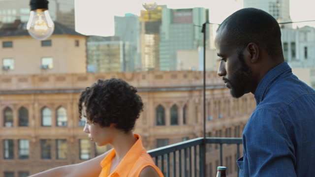 man bringing girlfriend a drink on roof terrace - bottle opener stock videos & royalty-free footage