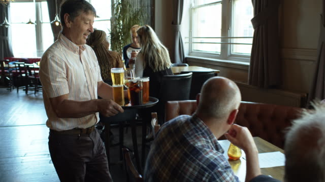 man bringing tray of drinks to friends at table in pub - pub stock videos & royalty-free footage