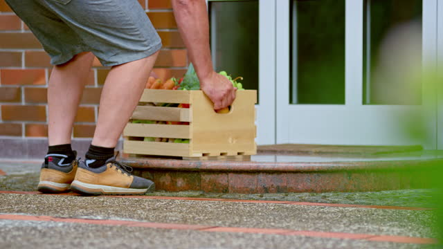 man brining a wooden crate with fresh produce on the doorstep of a family home - doorstep stock videos & royalty-free footage