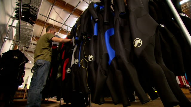 vídeos de stock, filmes e b-roll de a man browses wet suits hanging on a rack in a garment factory. - traje de mergulho