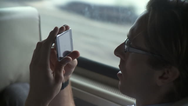 cu man browsing pictures on display of his portable media player in moving commuter train / new york city, new york, usa - interno di treno video stock e b–roll