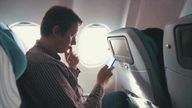 Man browsing smart phone on the airplane (slow motion)
