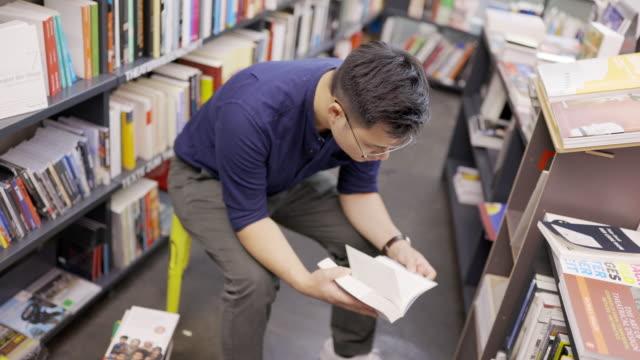 man browsing through books at a bookshop - korean ethnicity stock videos & royalty-free footage