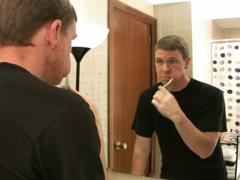 man brushes teeth in front of mirror - black shirt stock videos & royalty-free footage