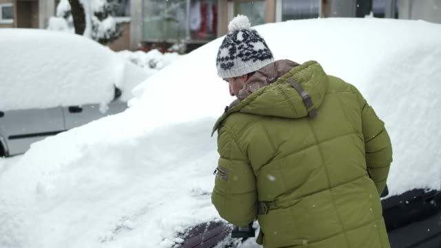 HD: Man Brushing Snow Off The Car