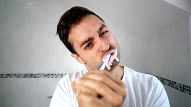 Man brushing teeth in the morning.