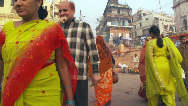 man brushing teeth with stick and walking on steps  as pin saris pass by. - donne di età media video stock e b–roll
