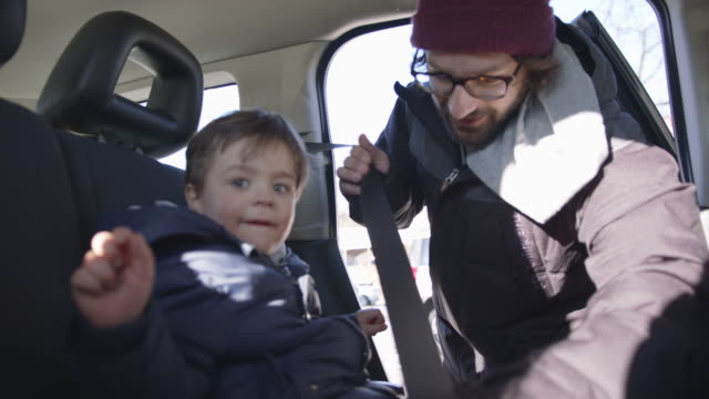 man buckles young boy's seat belt in vehicle - seat belt stock videos & royalty-free footage
