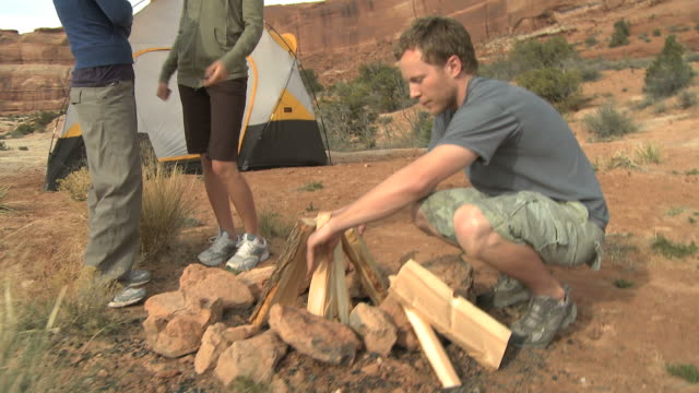 stockvideo's en b-roll-footage met man building a campfire as two woman talk at their campsite - man met een groep vrouwen