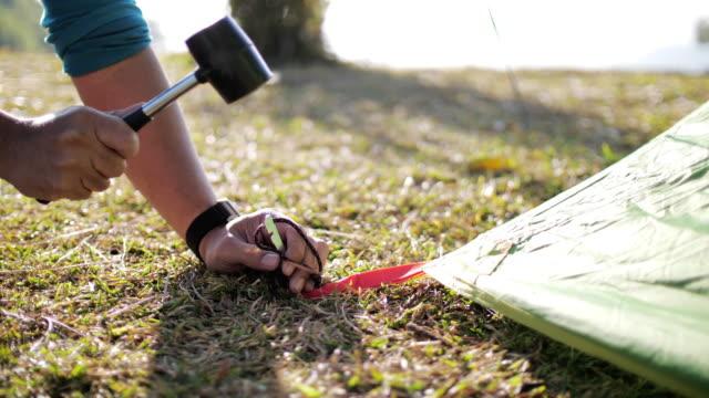 vídeos y material grabado en eventos de stock de acampada de man building en el área de camping - construir