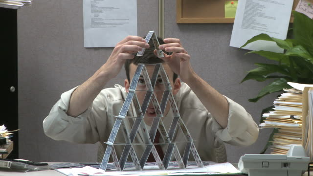 man building house of cards