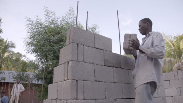 man builds wall with cinder blocks after 2010 earthquake no - rebuilding stock videos and b-roll footage