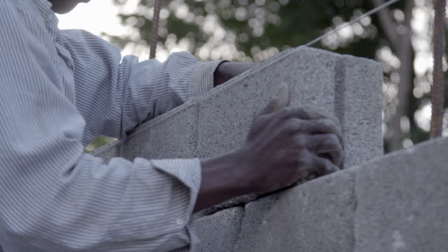 man builds wall with cinder blocks after 2010 earthquake no - rebuilding stock videos & royalty-free footage