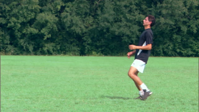 Man bumping with chest and kicking soccer ball