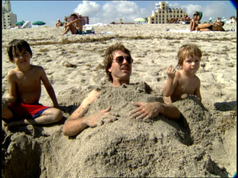 vídeos de stock e filmes b-roll de man buried in sand with two kids in miami florida - enterrado