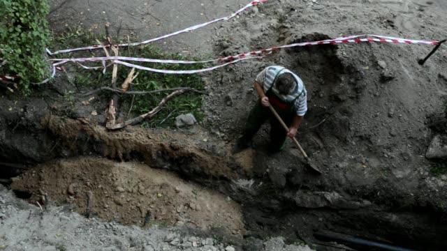 vidéos et rushes de l'homme enterre la tranchée avec le pipeline. - classe ouvrière