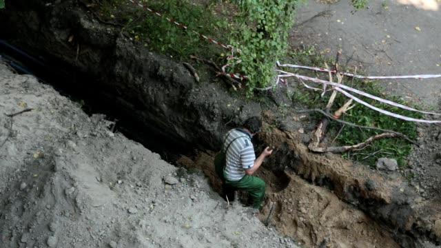 man buries the trench with the pipeline. - ukrainian ethnicity stock videos and b-roll footage