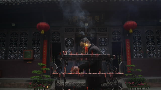 A man burns incense in front of the Chengdu Qing Yang Temple in Chengdu, China.