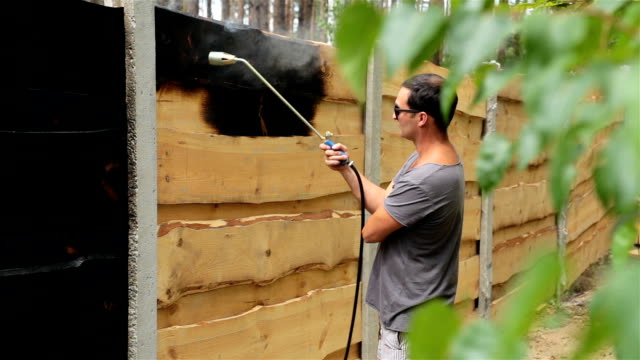 man burns the surface of the wooden fence. - timber stock videos and b-roll footage