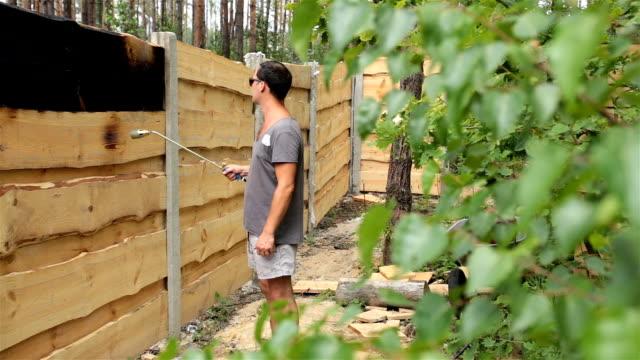 男は、木製の柵の表面を燃やします。 - ブンセン灯点の映像素材/bロール