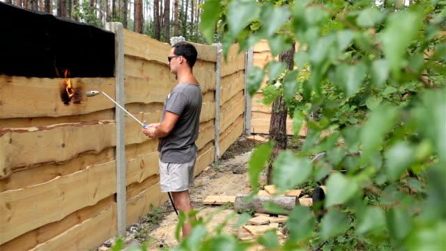 vídeos y material grabado en eventos de stock de hombre quema la superficie de la valla de madera. - un solo hombre de mediana edad