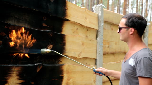 man burns the surface of the wooden fence. - bunsen burner stock videos & royalty-free footage