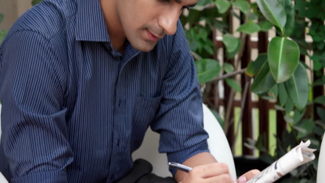 man busy filling a crossword in the newspaper at his home relaxed - crossword stock videos and b-roll footage